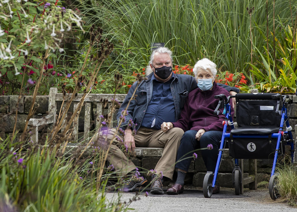 VANCOUVER, BRITISH COLUMBIA - OCTOBER 04: Two people wearing face masks sit on a bench at VanDusen Botanical Garden on October 04, 2020 in Vancouver, Canada. The Government of British Columbia has extended the Provincial State of Emergency until October 13, 2020 under the Emergency Program Act to support the Province's COVID-19 pandemic response. (Photo by Andrew Chin/Getty Images)