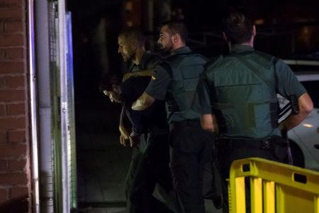 Spanish Civil Guards escort one of four men accused of involvement in an Islamist cell behind a van attack in Barcelona last week, in Tres Cantos, Spain, August 21, 2017. REUTERS/Juan Medina