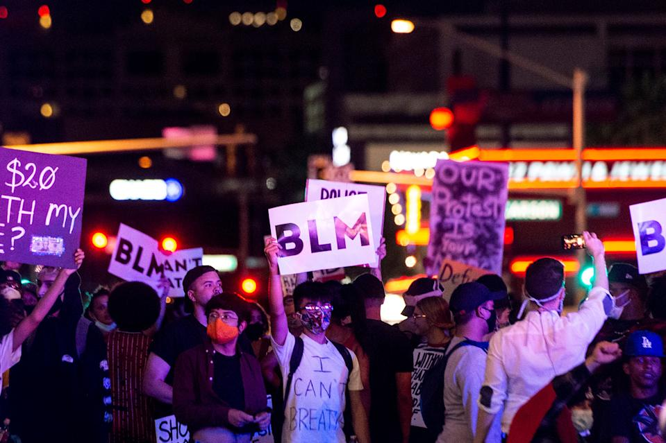 """People shout slogans and hold placards, on June 1, 2020, in downtown Las Vegas, as they take part in a """"Black lives matter"""" rally in response to the recent death of George Floyd, an unarmed black man who died while in police custody. Thousands of National Guard troops patrolled major US cities after five consecutive nights of protests over racism and police brutality that boiled over into arson and looting, sending shock waves through the country.  (Photo by Bridget Bennett/AFP via Getty Images)"""