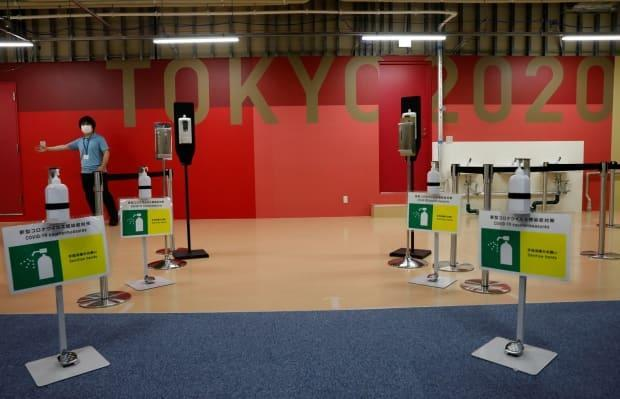 Hand sanitizers and signs for COVID-19 countermeasures are placed at the entrance of the fitness centre at the multi-function complex of the Olympic and Paralympic Village in Tokyo. (Kim Kyung-Hoon/Reuters - image credit)