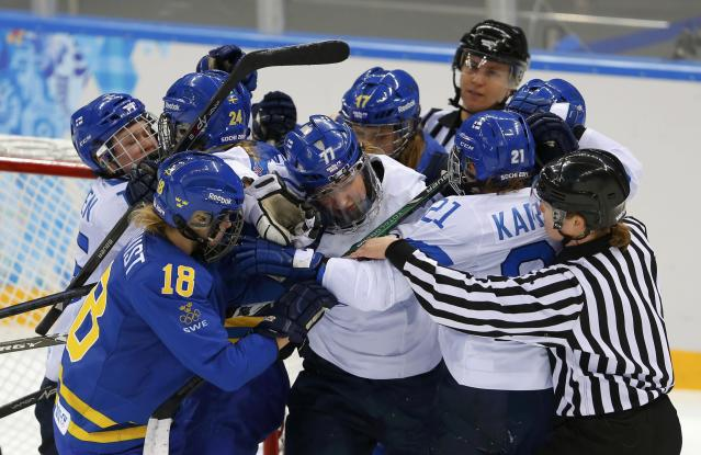 Referee jumps in to break up a scuffle between Sweden and Finland players during the second period of their women's ice hockey playoffs quarter-final game at the Sochi 2014 Winter Olympic Games February 15, 2014. REUTERS/Laszlo Balogh (RUSSIA - Tags: SPORT ICE HOCKEY OLYMPICS)