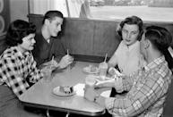<p>A pair of teenage couples gather at the parlor booth to enjoy ice cream soda floats.</p>