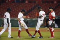 Boston Red Sox players, from left to right, Jackie Bradley Jr., Andrew Benintendi, Phillips Valdez and Jonathan Lucroy celebrate after defeating the Baltimore Orioles during an opening day baseball game at Fenway Park, Friday, July 24, 2020, in Boston. (AP Photo/Michael Dwyer)