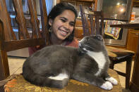 """In this photo provided by Raghav Ranjan, Devika Ranjan smiles at her cat, Aloo, on Dec. 13, 2020, in Andover, Mass. Ranjan, a theater director in Chicago, wanted pandemic company and got a rescue cat she named Aloo during the summer. The formerly feral cat is believed to be around 3, and seems to be very comfortable with a slow-paced, high-attention pandemic life. """"My working from home, I think he loves it,"""" she says. """"I think he is just ready to settle down in life. If he were human, he'd probably sit on the couch with a PBR (beer) and watch TV all day."""" (Raghav Ranjan via AP)"""