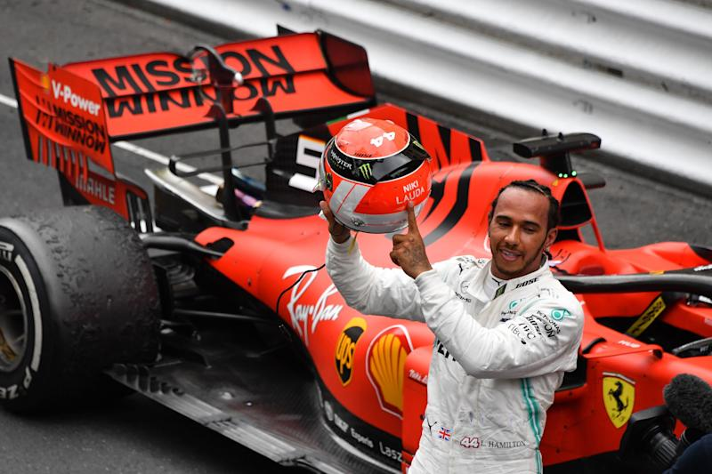 Lewis Hamilton points at the name of late F1 legend Niki Lauda after winning the Monaco GP (Photo credit should read YANN COATSALIOU/AFP/Getty Images)