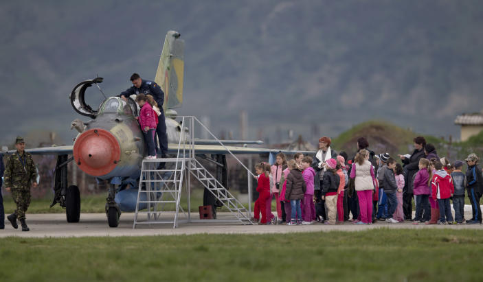 FILE - In this Thursday, April 10, 2014 file picture, Romanian children, visiting an airbase, wait to get a close look at a Soviet era Romanian MIG 21 fighter jet in Campia Turzii, Romania. The U.S. Air Force has deployed on Monday, Jan. 4, 2021, about 90 airmen and an unspecified number of drone aircraft to a base in central Romania, boosting its military presence in the region where there are allied concerns that Russia is trying to display its military strength. (AP Photo/Vadim Ghirda, File)