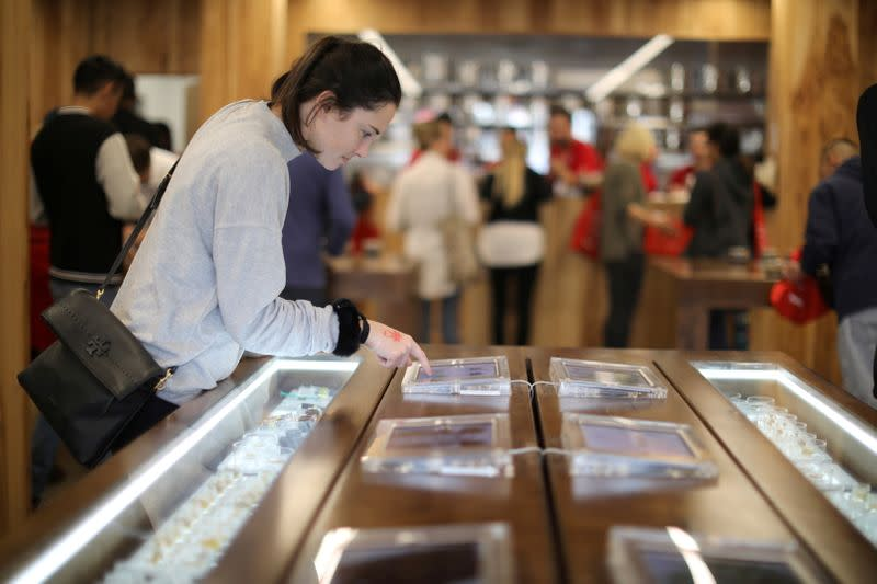 FILE PHOTO: A customer browses screens displaying recreational marijuana products for sale at the MedMen store in West Hollywood