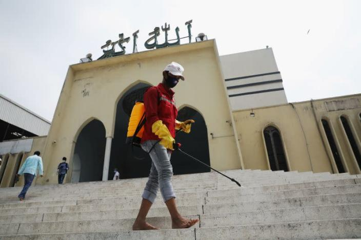 A volunteer sprays disinfectant in the Baitul Mukarram National Mosque before friday prayer amid concerns over the coronavirus disease (COVID-19) outbreak in Dhaka