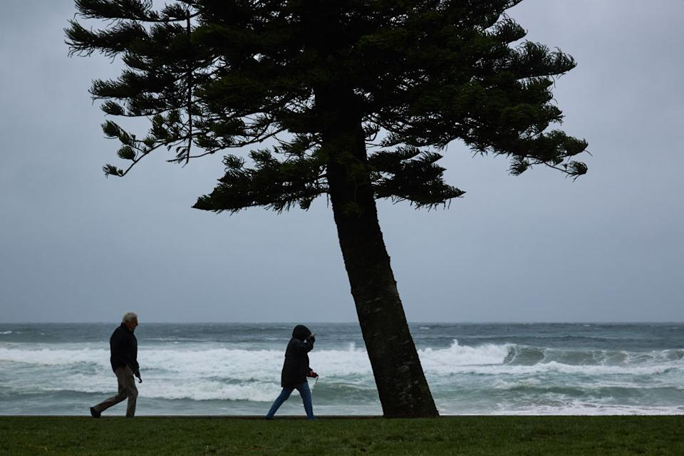 People walk in strong winds and rainy conditions at Manly Beach.
