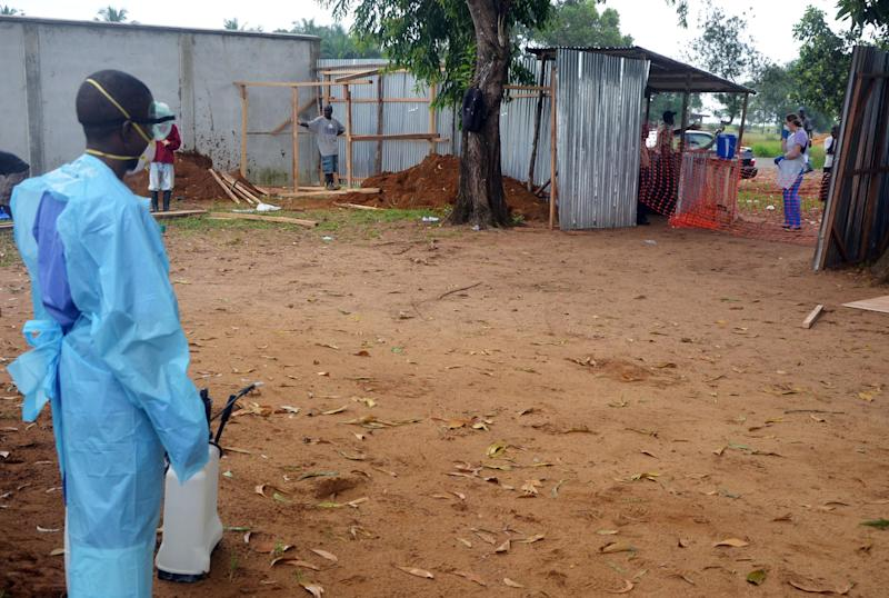 A staff member of the Christian charity Samaritan's Purse carries a spray gun as he disinfects the entrance to a hospital in the Liberian capital Monrovia, on July 24, 2014