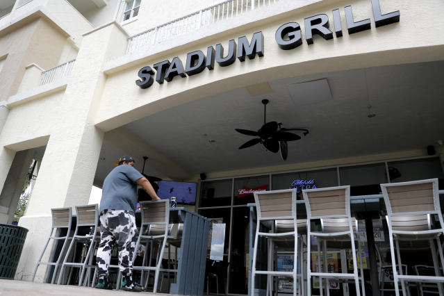 A person stands near empty seats at Stadium Grill, Monday, March 16, 2020, in Jupiter, Fla. The restaurant, which is across the street from Roger Dean Chevrolet Stadium, the spring training baseball home of the St. Louis Cardinals and the Miami Marlins, is normally full with customers on game day. On Sunday night, the Centers for Disease Control and Prevention recommended gatherings of 50 people or more be canceled or postponed across the country for the next eight weeks. Major League Baseball planned to update teams Monday on its health policy. (AP Photo/Julio Cortez)