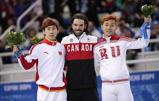 Charles Hamelin of Canada, centre, Han Tianyu of China, left, and Victor An of Russia pose on the podium during the flower ceremony for the men's 1500m short track speedskating final at the Iceberg Skating Palace during the 2014 Winter Olympics, Monday, Feb. 10, 2014, in Sochi, Russia. Hamelin placed first, Han second and An third. (AP Photo/Bernat Armangue)