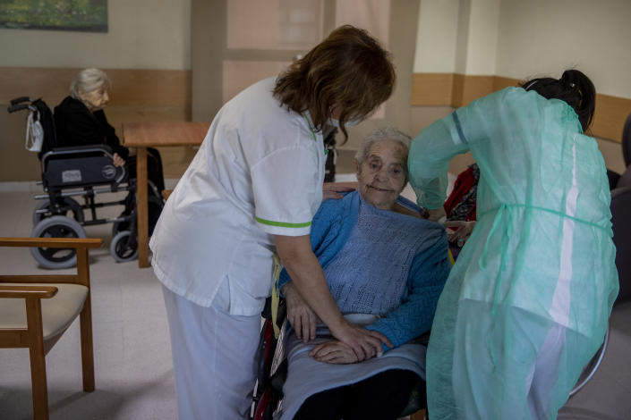 A nurse administers the Pfizer-BioNTech COVID-19 vaccine to a resident at DomusVi nursing home in Leganes, Spain, Wednesday, Jan. 13, 2021. Spain's rate of infection has shot up to 435 cases per 100,000 residents in the past two weeks, prompting new restrictions as authorities try to bring vaccination up to speed. (AP Photo/Manu Fernandez)