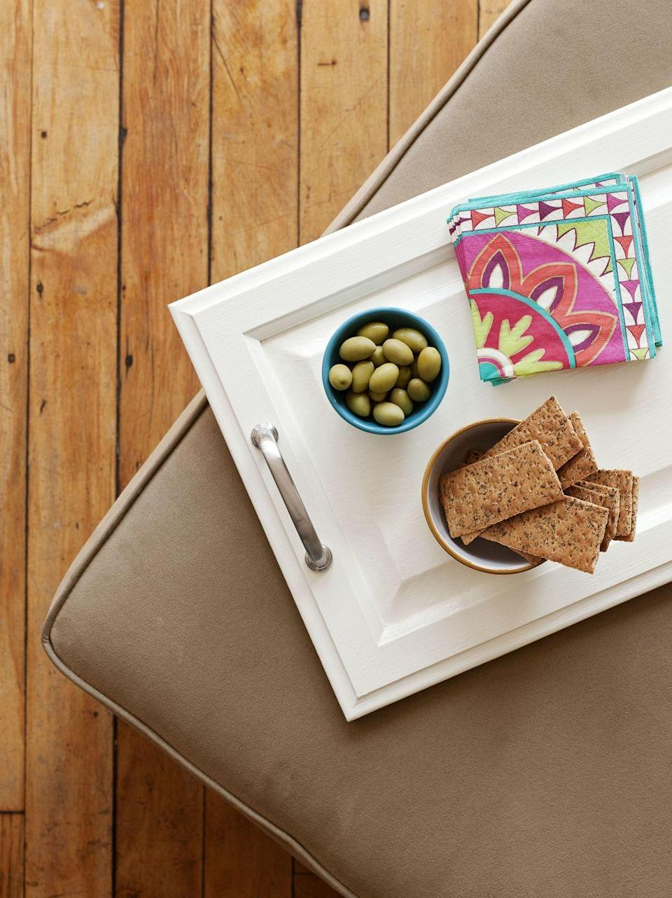 <p>With paint and a pair of drawer pulls, a salvaged cabinet door becomes a makeshift cheese board or TV dinner tray. To make, fill holes in the board with wood filler and let dry. Sand and paint the surface, pre-drill holes, and screw in handles. </p>