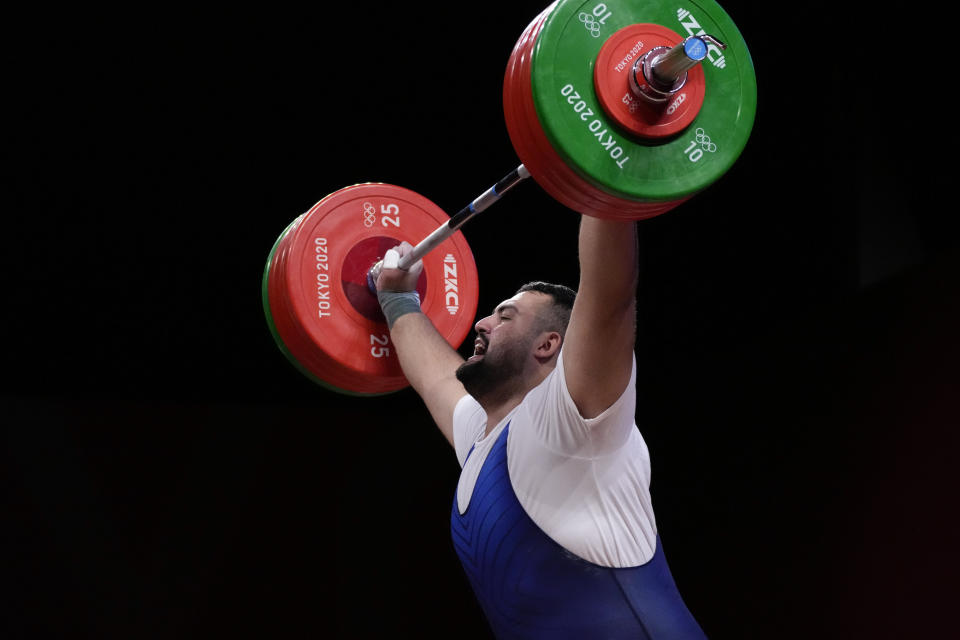 Alii Davoudi of Iran competes in the men's +109kg weightlifting event, at the 2020 Summer Olympics, Wednesday, Aug. 4, 2021, in Tokyo, Japan. (AP Photo/Luca Bruno)