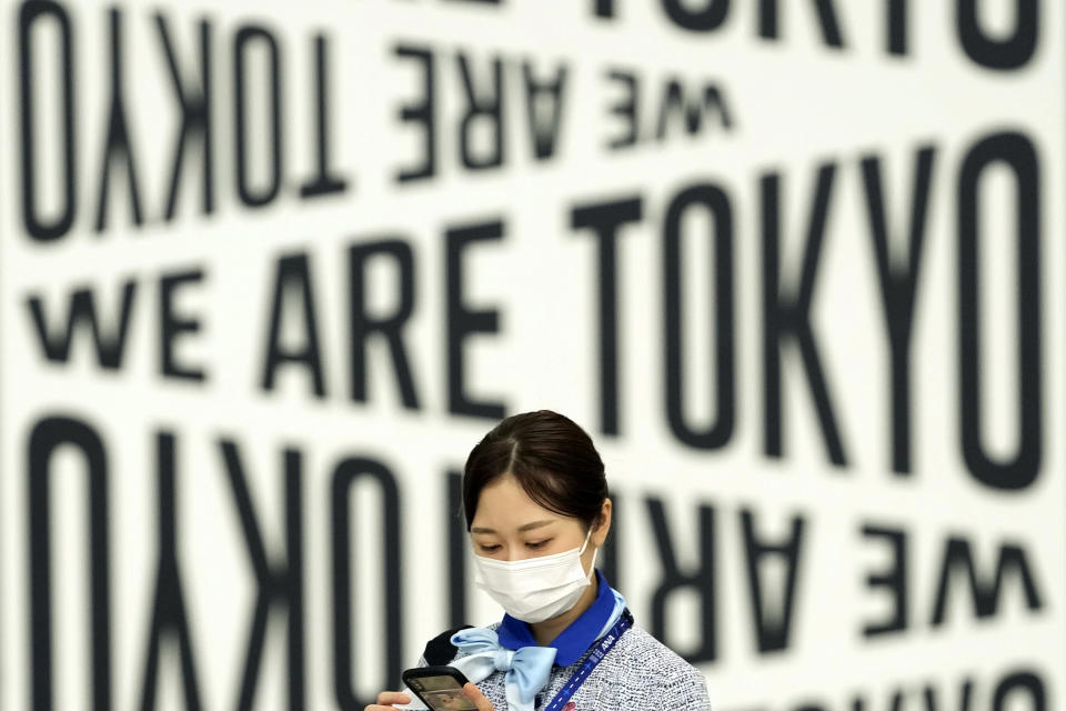 An employee wearing a protective mask to help curb the spread of the coronavirus walks through Haneda Airport Monday, Aug. 2, 2021, in Tokyo. (AP Photo/Eugene Hoshiko)