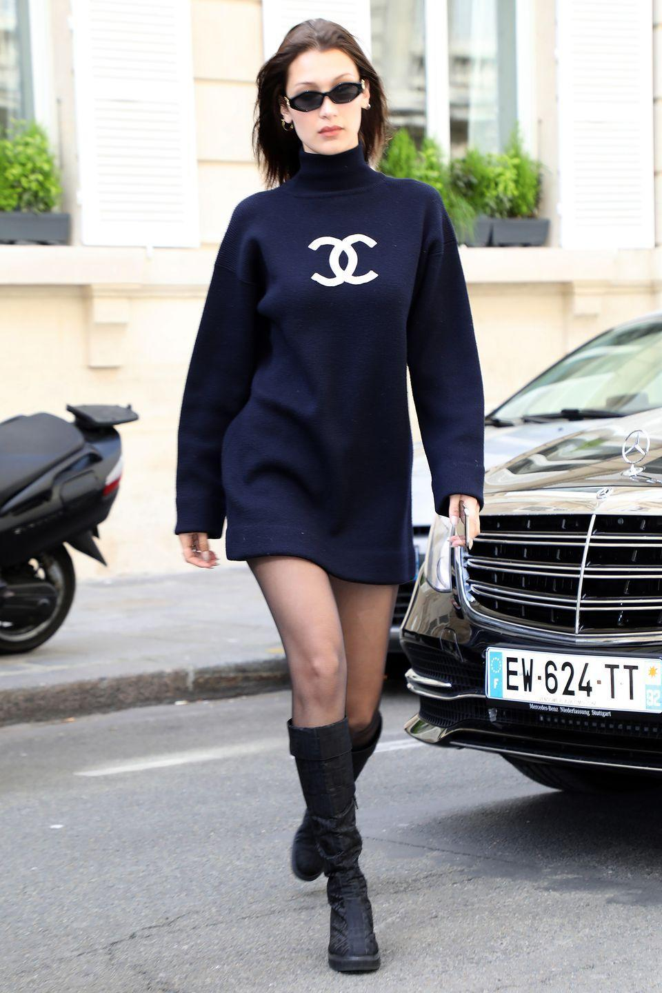 <p>wearing a black sweatshirt minidress by Chanel, sheer tights, casual slouchy boots, and Le Specs x Jordan Askill sunglasses while out in Paris.</p>