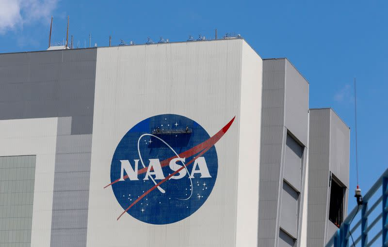 FILE PHOTO: Workers pressure wash the logo of NASA on the Vehicle Assembly Building, in Cape Canaveral
