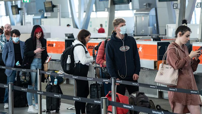 Travellers seen lining up at Sydney domestic airport wearing masks.