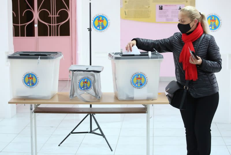 A woman casts her ballot at a polling station during the second round of a presidential election in Chisinau