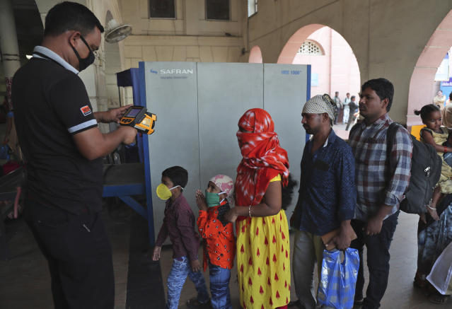 Indian passengers are screened for body temperature as a precautionary measure against COVID-19 at Secunderabad Railway Station in Hyderabad, India, Saturday, March 21, 2020. For most people, the new coronavirus causes only mild or moderate symptoms. For some it can cause more severe illness. (AP Photo/Mahesh Kumar A.)