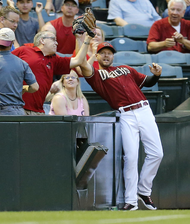 Arizona Diamondbacks' Cody Ross catches a foul ball hit by Colorado Rockies' Troy Tulowitzki around a fan during the first inning of a baseball game on Wednesday, April 30, 2014, in Phoenix. (AP Photo/Matt York)