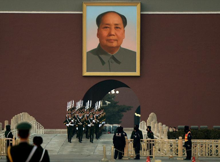 Chinese paramilitary police march beneath a portrait of late leader Mao Zedong beside Tiananmen Square in Beijing, on December 13, 2013