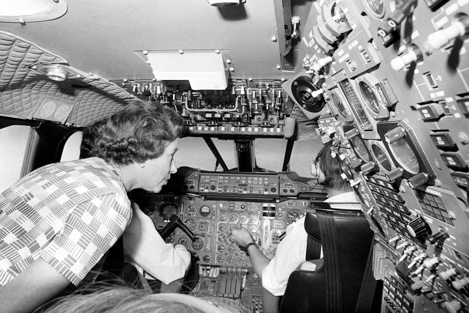 Queen Elizabeth II taking a close look at the crowded banks of instruments when she paid a visit to the flight deck of Concorde during her flight home from Bridgetown, Barbados, in the supersonic jetliner after her Silver Jubilee tour of the West Indies.