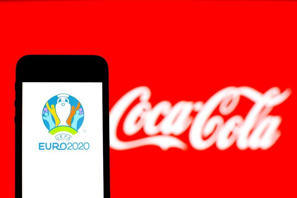 UEFA Euro 2020 logo seen displayed on a smartphone with a Coca-Cola logo in the background.