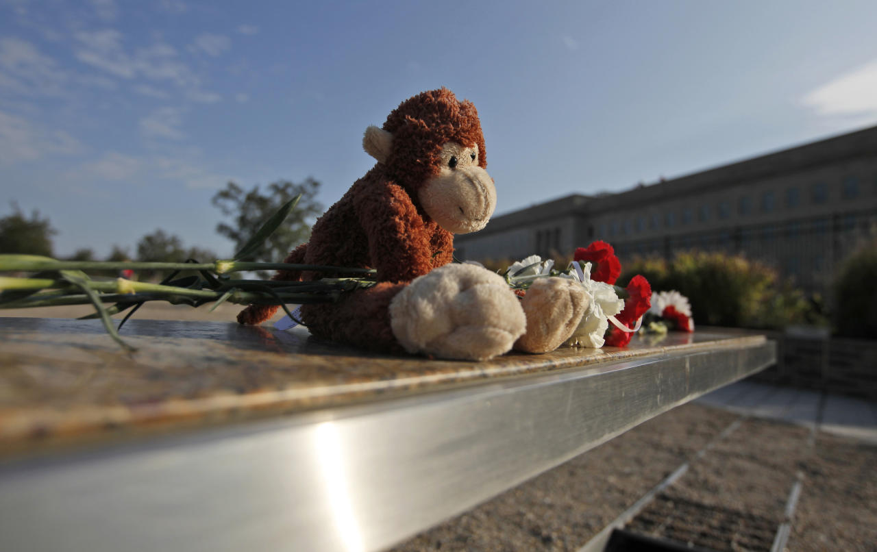 A stuffed toy and flowers are left on the bench at the Pentagon Memorial for Dana Falkenberg of University Park, Md., who was three when she died on American Flight 77 when it crashed into the Pentagon, ahead of the 10th anniversary of the Sept. 11 attacks, Saturday, Sept. 10, 2011. (AP Photo/Charles Dharapak)