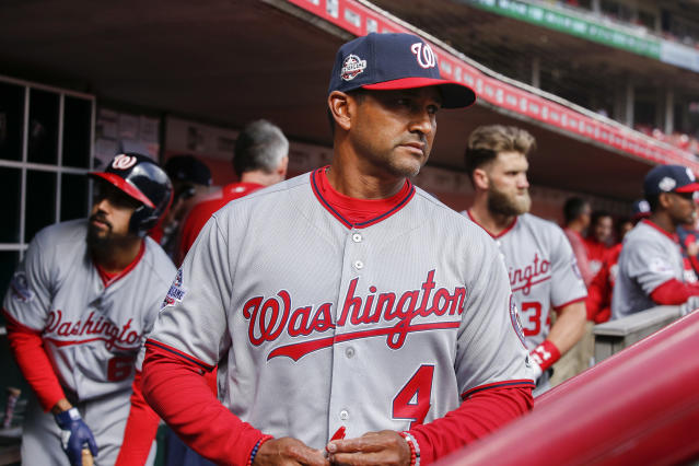 Washington Nationals manager Dave Martinez watches from the dugout before an opening day baseball game against the Cincinnati Reds, Friday, March 30, 2018, in Cincinnati. (AP Photo/Gary Landers)