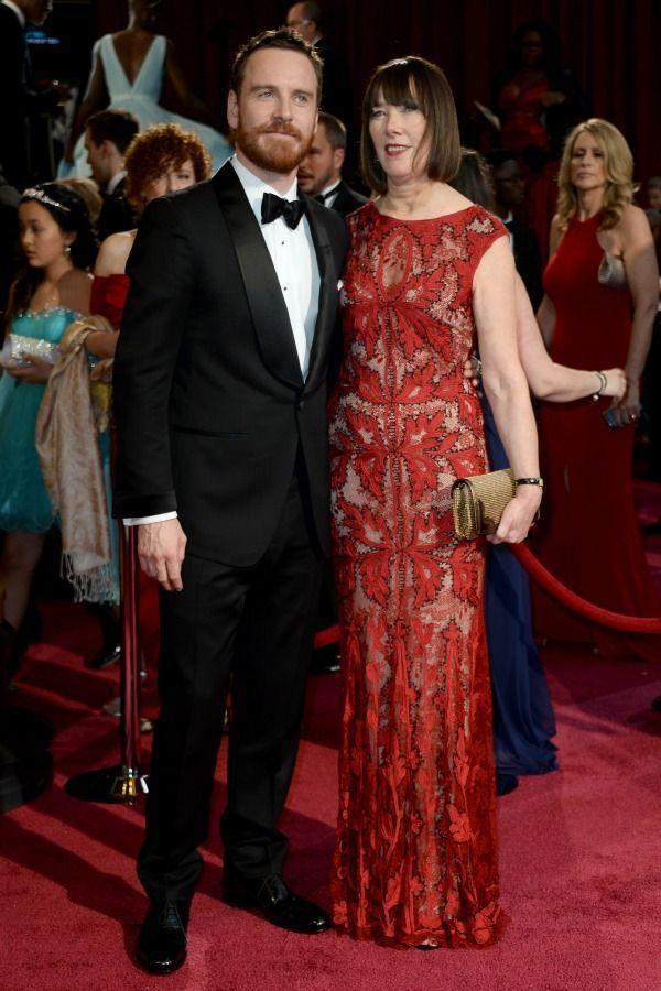 """<p>Micheal's mother, Adele Fassbender, brought the heat to the 2014 Oscars' <a href=""""https://www.redbookmag.com/fashion/features/g1075/red-carpet-fashion/"""" rel=""""nofollow noopener"""" target=""""_blank"""" data-ylk=""""slk:red carpet"""" class=""""link rapid-noclick-resp"""">red carpet</a> in her stunning red dress. </p>"""