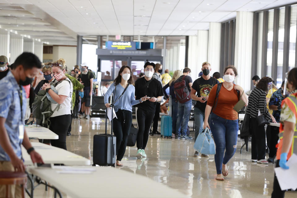 Visitors arrive at the airport Thursday, Oct. 15, 2020, in Honolulu. A new pre-travel testing program will allow visitors who test negative for COVID-19 to come to Hawaii and avoid two weeks of mandatory quarantine goes into effect Thursday. The pandemic has caused a devastating downturn on Hawaii's tourism-based economy. Coronavirus weary residents and struggling business owners in Hawaii will be watching closely as tourists begin to return to the islands. (AP Photo/Marco Garcia)