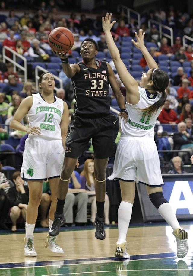 Florida State's Natasha Howard (33) shoots between Notre Dame's Natalie Achonwa (11) and Taya Reimer (12) during the first half of an NCAA college basketball game at the Atlantic Coast Conference tournament in Greensboro, N.C., Friday, March 7, 2014. (AP Photo/Chuck Burton)