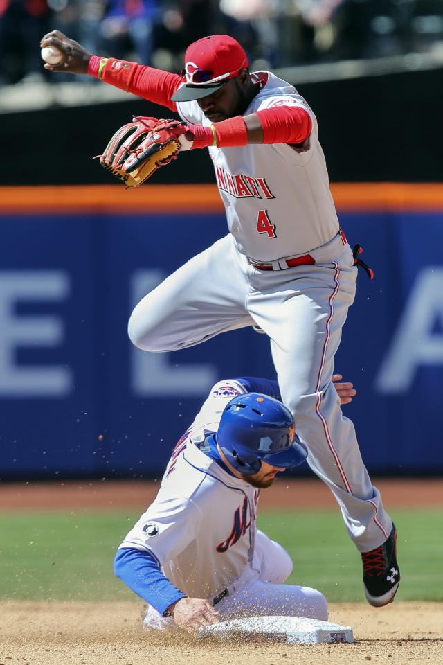 Cincinnati Reds second baseman Brandon Phillips (4) leaps over New York Mets' Daniel Murphy after making the out in the sixth inning of a baseball game at Citi Field, Saturday, April 5, 2014, in New York. (AP Photo/John Minchillo)