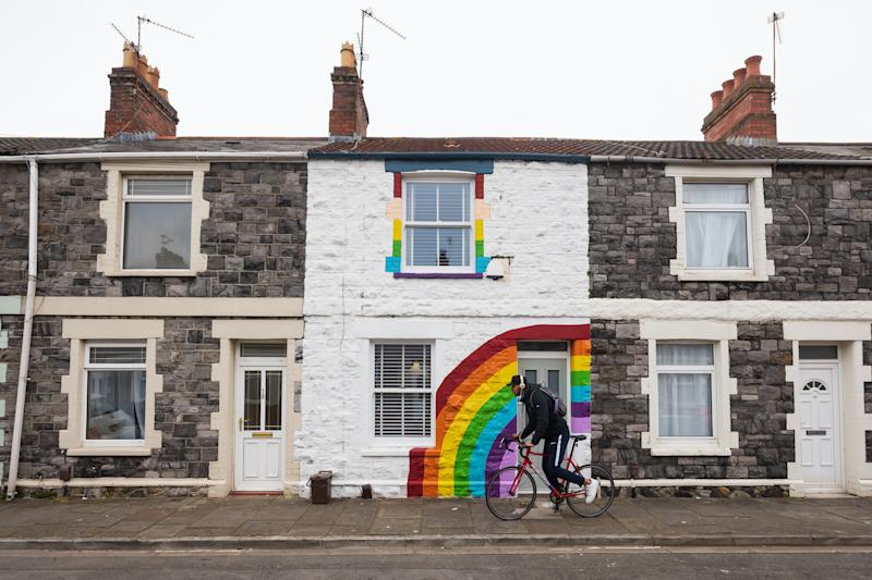 CARDIFF, WALES - APRIL 02: A man rides his bike passed a terraced house painted with a rainbow in support of the National Health Service (NHS) on Gwendoline Street in Splott on April 2, 2020, in Cardiff, Wales. The Coronavirus (COVID-19) pandemic has spread to many countries across the world, claiming over 45,000 lives and infecting hundreds of thousands more. (Photo by Matthew Horwood/Getty Images)