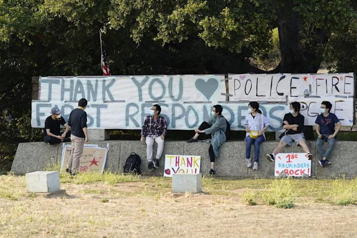 Students and researchers at UC Santa Cruz sit in front of a sign thanking first responders, on 24 August.