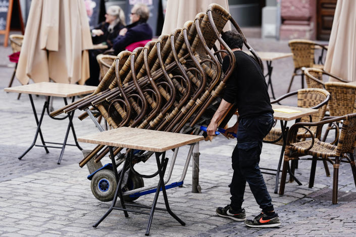 The employee of a pub rolls a stack of chairs onto the market place in Heidelberg, Germany, Saturday, May 15, 2021. After months of lockdown, the Southwest is loosening the reins on Corona rules significantly. From Saturday on, openings in gastronomy, tourism and leisure are possible. (Uwe Anspach/dpa via AP)