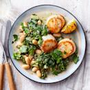 """<p>This recipe for seared scallops with white beans and spinach turns out a healthy dinner that looks impressive (and tastes great) in just 25 minutes. Giving lemons a quick sizzle in the skillet amps up the flavor of this piccata-inspired dish. The heat helps release even more citrus juice and sweetens it too. When shopping for scallops, look for ones labeled """"dry."""" Some scallops are soaked in a solution that prevents them from searing properly and can give them a soapy flavor.</p>"""