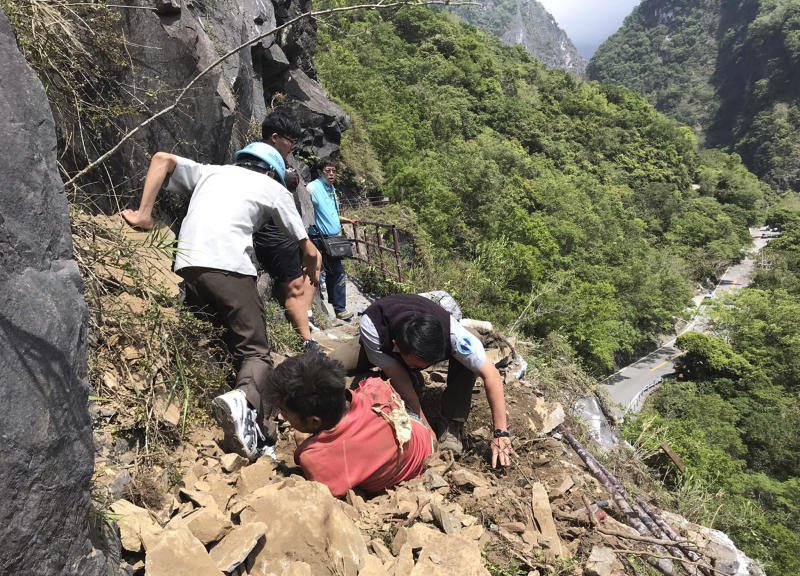 In this photo released by Taroko National Park, an injured Malaysian tourist, in red, is assisted by rescue workers at the Taroko National Park in Hualien in eastern Taiwan Thursday, April 18, 2019. A strong earthquake rattled eastern Taiwan early Thursday afternoon, causing scattered light damage in the capital and the eastern coast region. (Taroko National Park via AP)