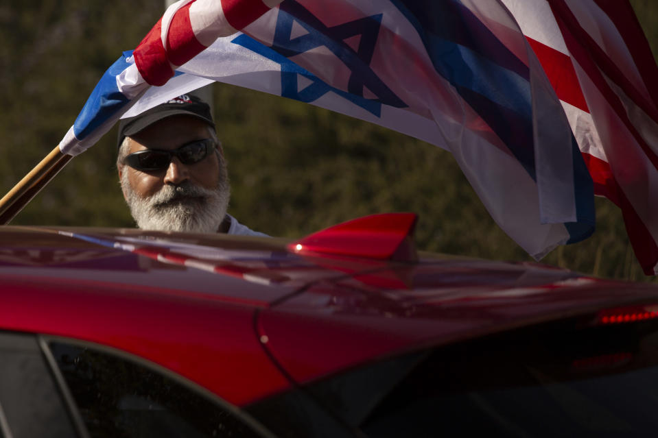 An Israeli supporter of the re-election of U.S. President Donald Trump waves American and Israeli flags from a car at a rally outside of the U.S. Embassy, in Jerusalem, Tuesday, Oct. 27, 2020. (AP Photo/Maya Alleruzzo)
