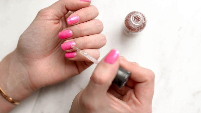 painting manicured nail with pink and glitter