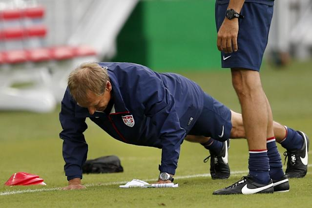 United States' head coach Jurgen Klinsmann does push-ups before an official training session the day before the group G World Cup soccer match between Ghana and the United States at the Arena das Dunas in Natal, Brazil, Sunday, June 15, 2014. (AP Photo/Julio Cortez)