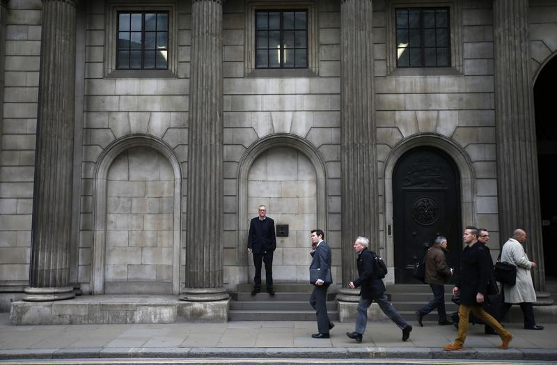 A man smokes a cigarette outside The London Stock Exchange