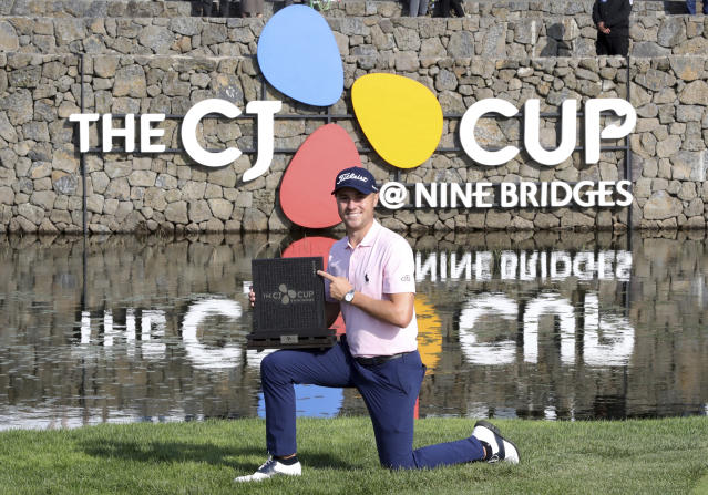 Justin Thomas of the United States poses with his trophy after winning the CJ Cup PGA golf tournament at Nine Bridges on Jeju Island, South Korea, Sunday, Oct. 20, 2019. (Chun Jin-hwan/Newsis via AP)