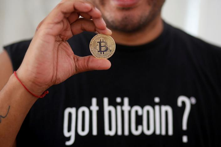 Bitcoin enthusiast Carlos Bonilla shows a physical representation of the cryptocurrency, at a Bitcoin Beach support office at El Zonte Beach in Chiltiupan, El Salvador June 10, 2021. Picture taken June 10, 2021. REUTERS/Jose Cabezas REFILE - CORRECTING INFORMATION