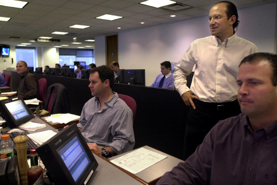 FILE - In this Wednesday, Aug. 28, 2002 file photo, Howard Lutnick, standing, chief executive of Cantor Fitzgerald, watches trading conducted on the trading floor of the company's New York office. The company lost about two thirds of its nearly 1,000 employees headquartered in the World Trade Center when the towers collapsed after attacks on Sept. 11, 2001. (AP Photo/Bebeto Matthews, File)