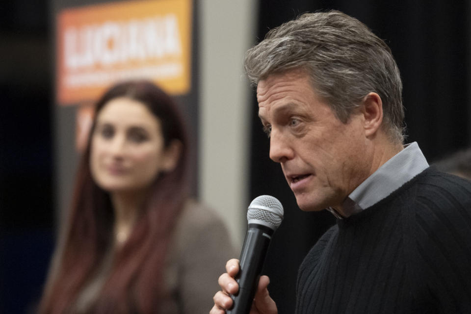 Britain's Liberal Democrat Party candidate for Finchley and Golders Green, Luciana Berger, left, listens to actor Hugh Grant speak during a canvassing event in north London, Sunday Dec. 1, 2019, ahead of the general election on Dec. 12. (David Mirzoeff/PA via AP)