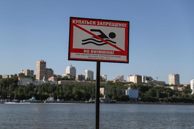 """A """"No swimming"""" sign is seen at a beach on the Don River near Rostov Arena in Rostov-on-Don, Russia June 15, 2018. As well as shooting all the matches, Reuters photographers are producing pictures showing their own quirky view from the sidelines of the World Cup. REUTERS/Marko Djurica"""
