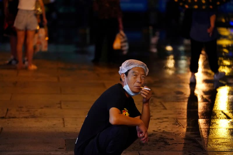 FILE PHOTO: Man smokes with a mask on his chin following the coronavirus disease (COVID-19) outbreak, during a rainfall in Beijing